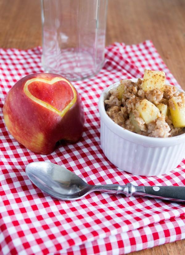 Apfelkuchen-Porridge mit Zimt in einer weißen Schüssel, ein Apfel mit Herz in der Schale daneben