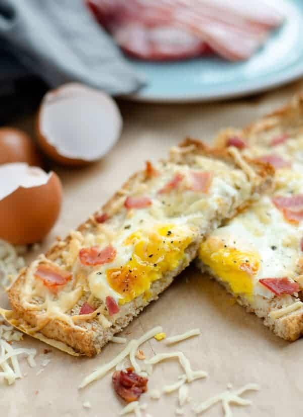 zwei halbe Scheiben Toast mit Ei, Bacon und Käse auf Backpapier