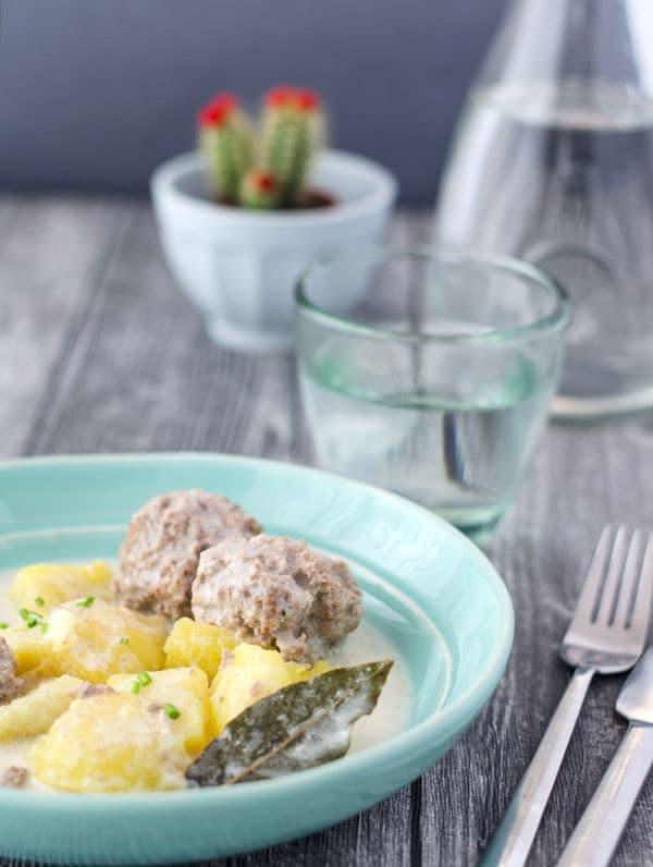 Königsberger Klopsemit Kartoffeln und Lorbeerblatt in hellblauer Schale