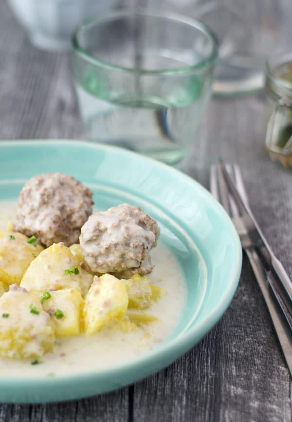 Königsberger Klopse mit Kartoffeln  auf einem türkisfarbenen Teller