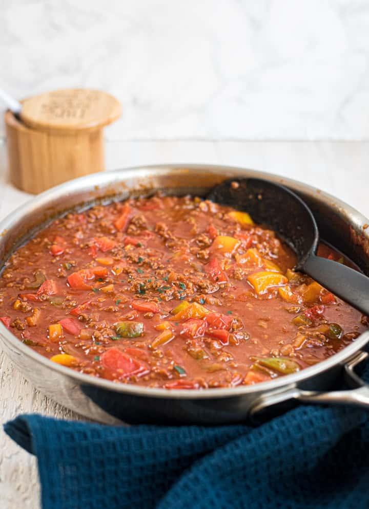 Paprika-Hackpfanne mit Tomatensauce in einer Pfanne mit einem Servierlöffel