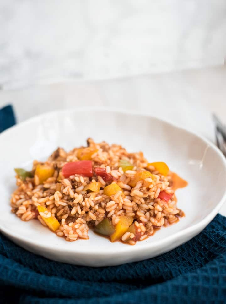 Paprika-Hackpfanne mit Reis auf einem weißen tiefen Teller.