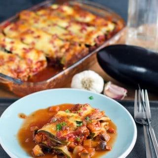 Zucchini Lasagne auf einem hellblauen Teller mit Auflaufform im Hintergrund