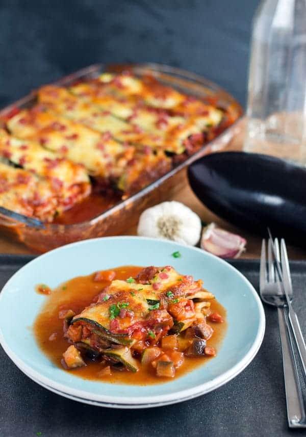 Ein Stück Zucchini Lasagne auf einem hellblauen Teller, Auflaufform im Hintergrund.