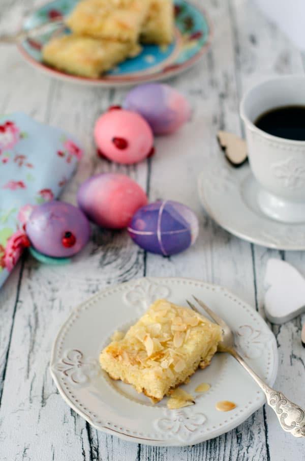Ein Stück Butterkuchen auf einem weißen Teller mit einer Gabel und Tasse im Hintergrund