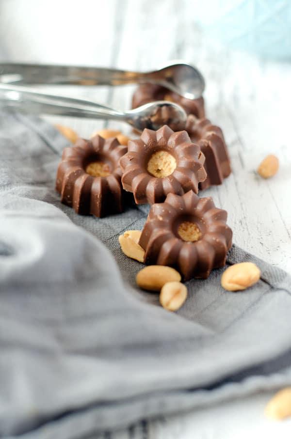 Viele Peanutbutter Cups auf einem hellen Untergrund mit Erdnüssen auf dem Bild