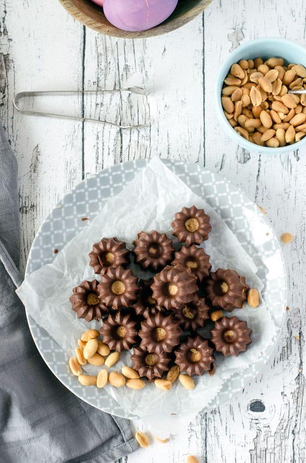 Viele Peanutbutter Cups auf einem hellen Untergrund mit Erdnüssen auf dem Bild von oben fotografiert