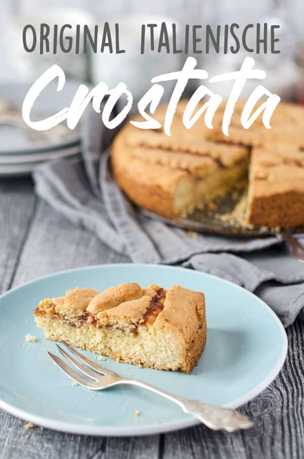 Ein Stück Crostata mit Marmelade auf einem Teller, der restliche Kuchen im Hintergrund