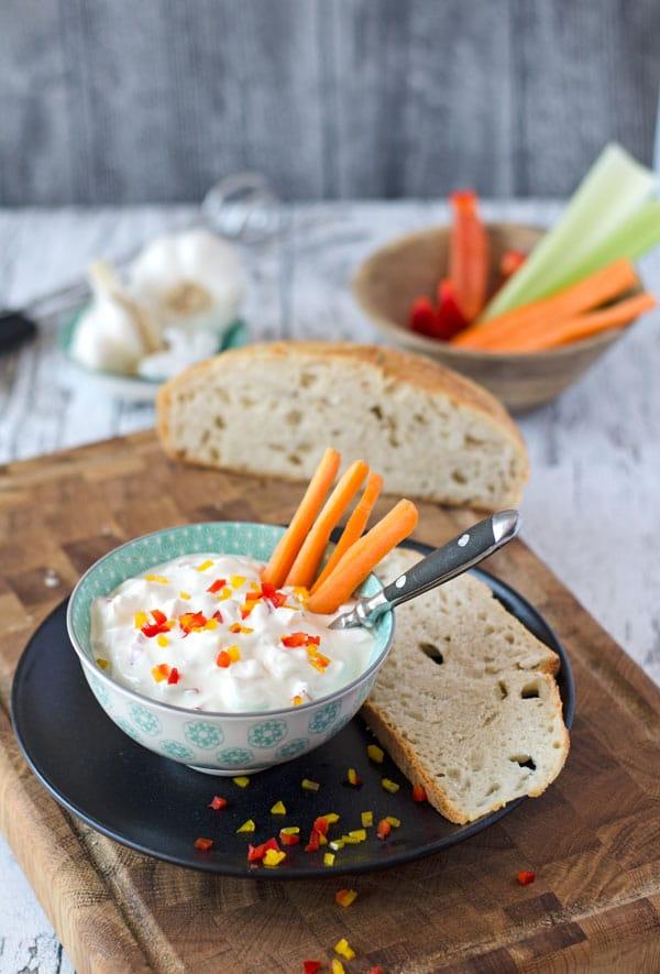 Paprika Dip in einer blau-weißen Schale mit Karottensticks und Brot
