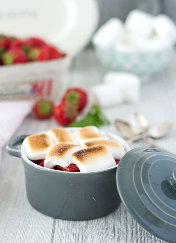 Eine graue Schale mit Erdbeeren und goldbraun gebackenen Marshmallows