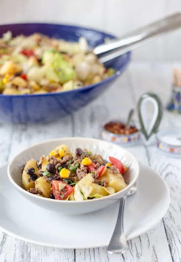 mexikanischer Kartoffelsalat in einer kleinen Schale, große dunkelblaue Schale im Hintergund