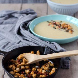 einfache Pastinakensuppe mit Chorizo, Croutons und Kürbiskerntopping.