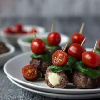Hackbällchen mit Tomate und Basilkum aufgespießt auf einem weißen Teller