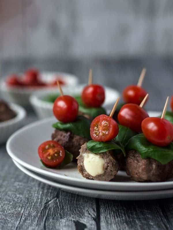 Caprese meatballs, filled with mozzarella, topped with tomato and basil. super fingerfood. Recipe also in english!