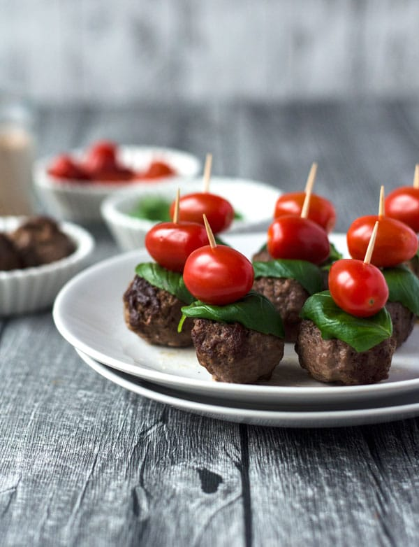 weißer Teller mit Hackbällchenspießen mit Basilikum und Tomate