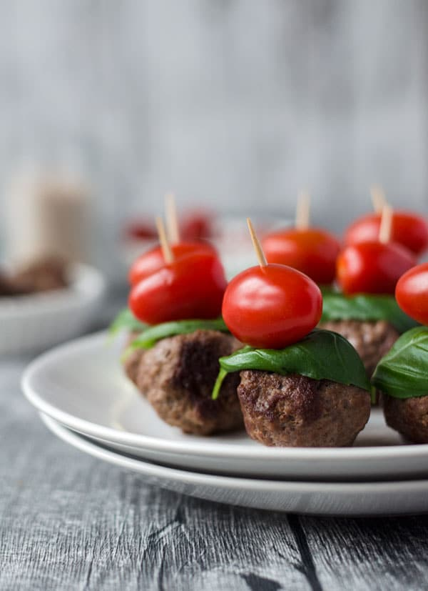 Nahaufnahme der Hackbällchen mit Basilikum und Tomate aufgespießt