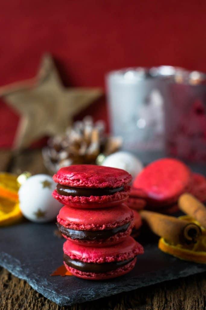 Drei rote Schoko-Orangen-Macarons aufeinander.