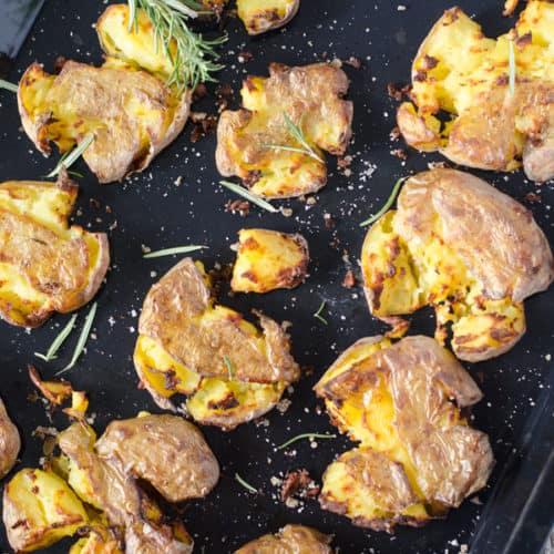 Zerdrückt und gebackene Kartoffeln auf einem Backblech, von oben fotografiert