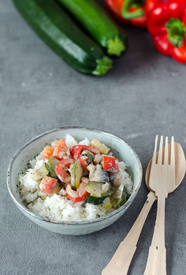 Reis mit Gemüse und Frischkäsesauce in einer gesprenkelten Schale
