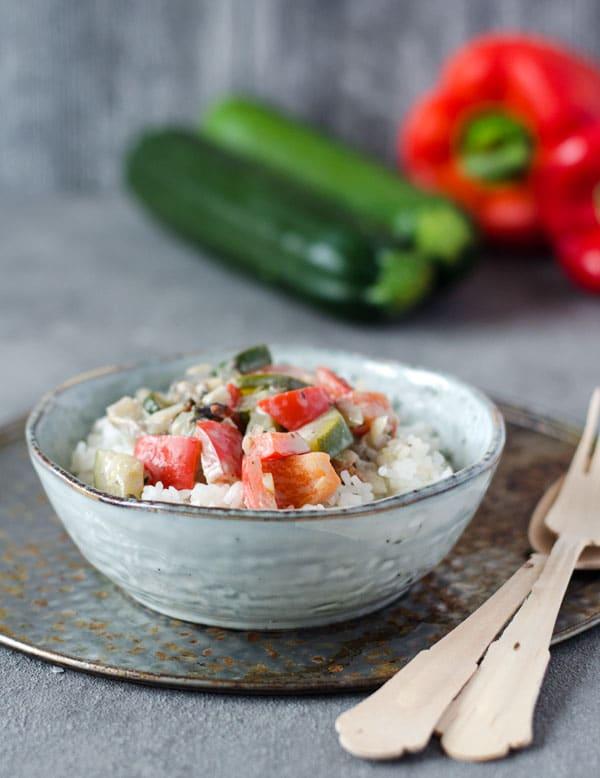 Gemüsepfanne auf Reis in einer kleinen Schale mit Gemüse im Hintergrund