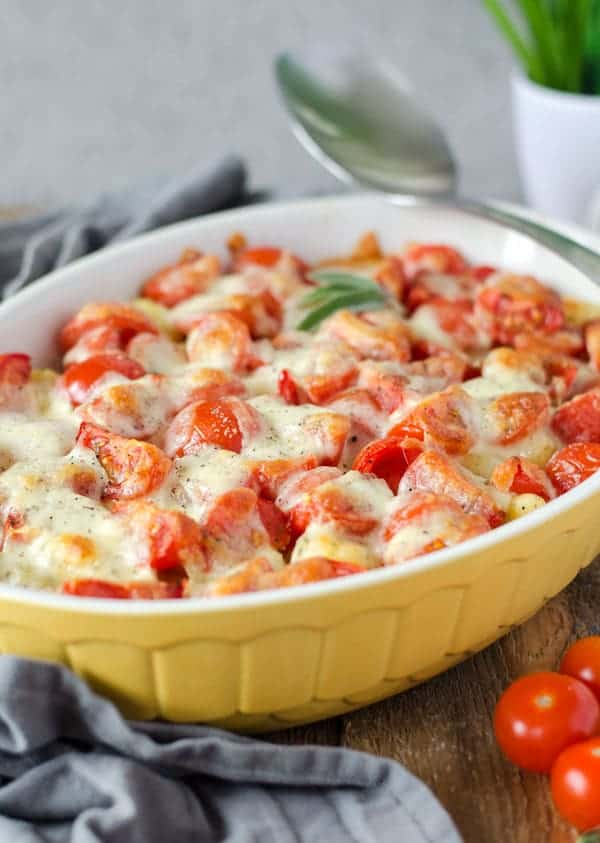 Gnocchi-Auflauf mit Tomaten und Mozzarella überbacken in einer gelben Auflaufform.