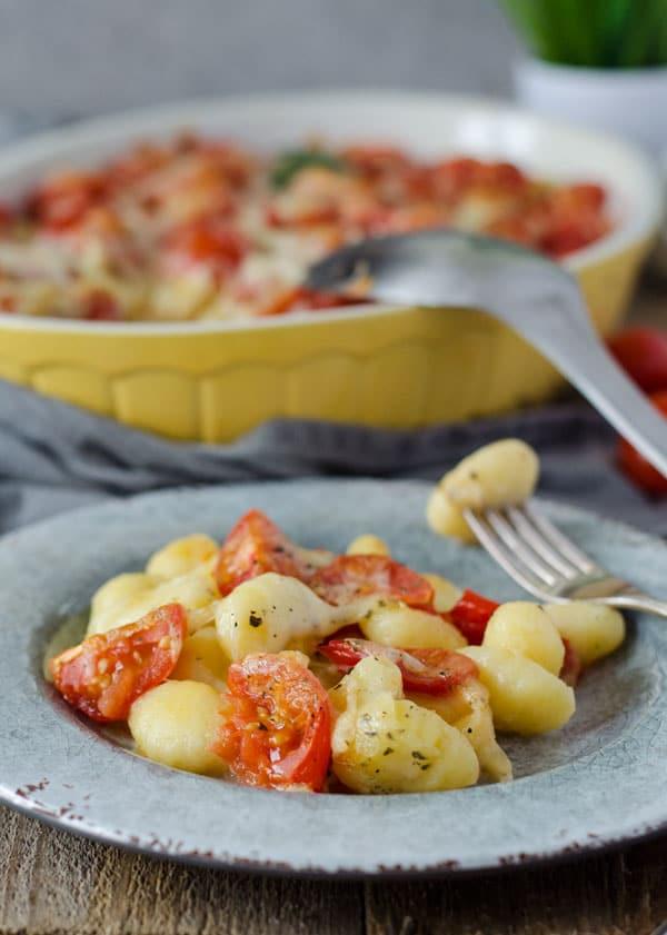 Gnocchi-Auflauf mit Tomaten und Mozzarella überbacken auf einem Teller.