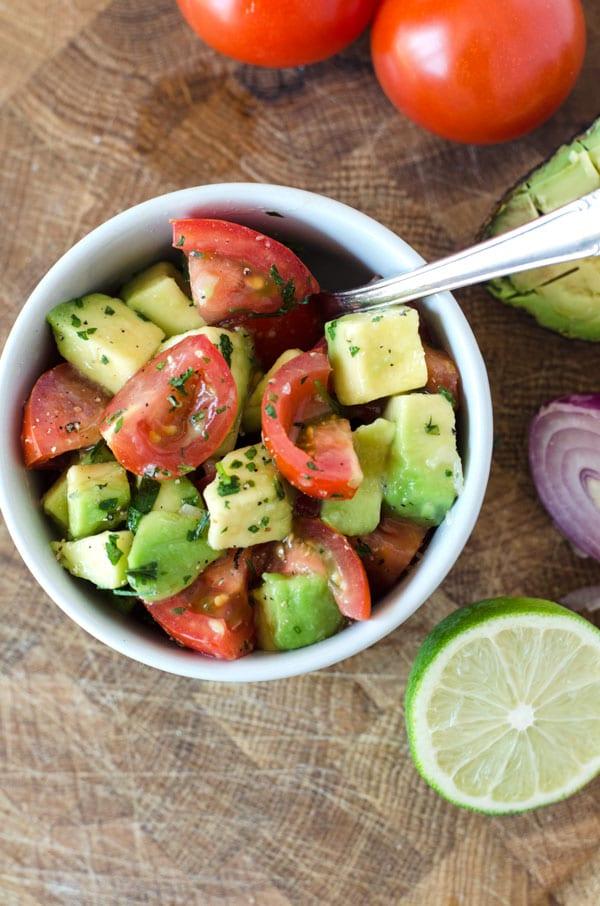 Nahaufnahme von oben vom Tomatensalat mit Avocado in hellgrauer Schüssel