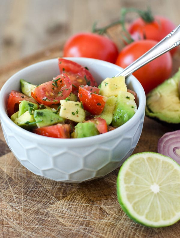 Tomaten-Avocado-Salat mit Petersilie in hellgrauer Schüssel und Limettendeko.