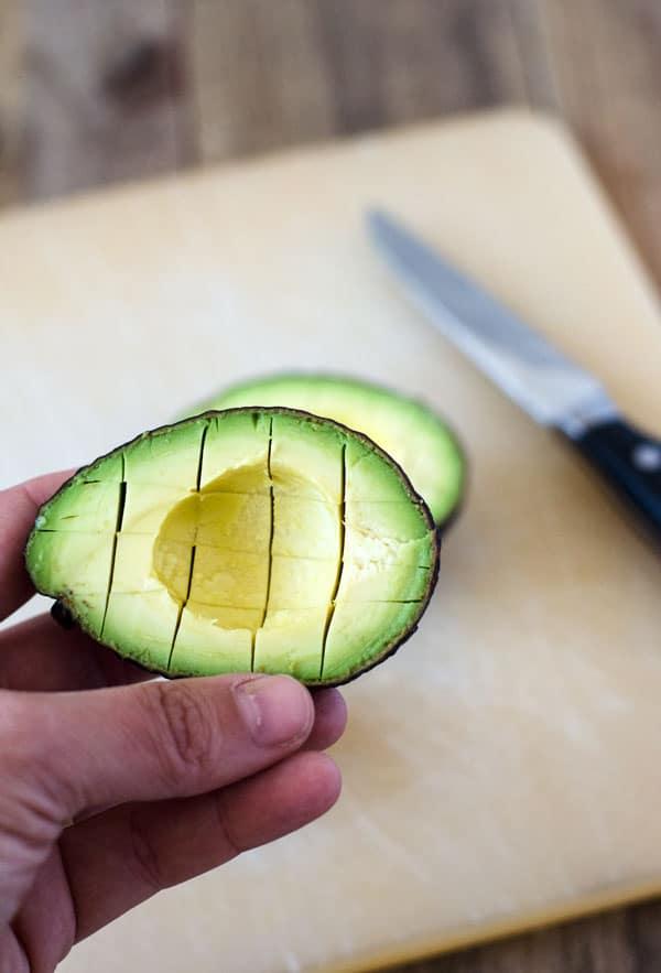 so schneidest du eine Avocado, halbieren, kreuzförmig einschneiden und auslöffeln.