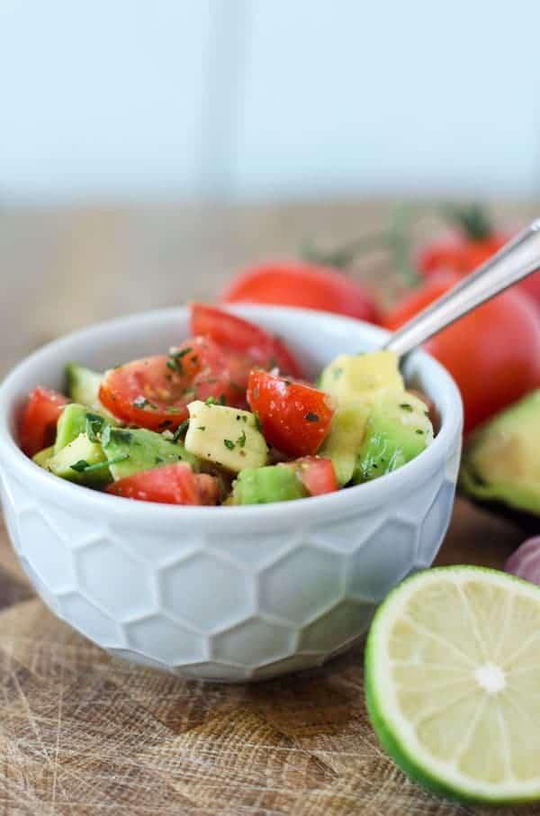 Tomaten-Avocado-Salat in einer hellgrauen Schüssel mit Limette dekoriert