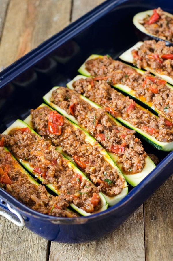 Mit Hackfleisch gefüllte Zucchinihälften in einer Auflaufform, von oben fotografiert