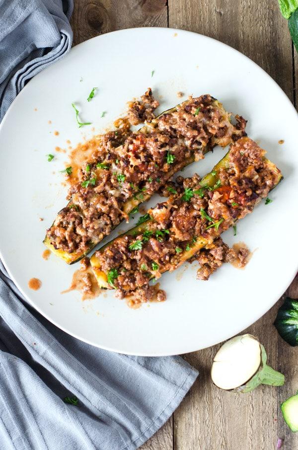 Zwei mit Hackfleisch gefüllte Zucchinihälften auf einem weißen Teller von oben fotografiert
