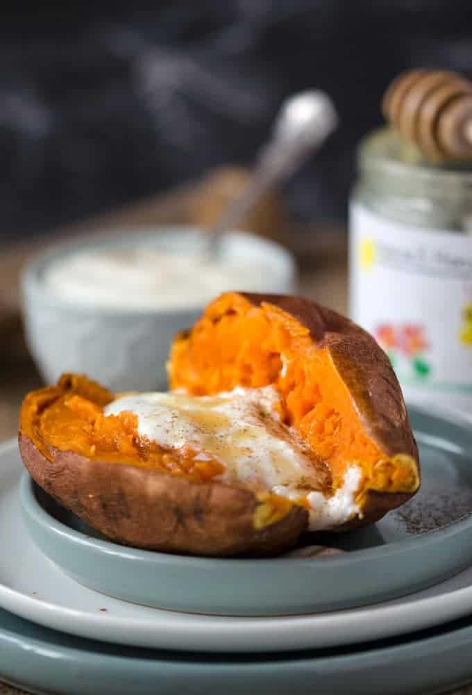 Süßkartoffel halbiert mit Jogurt und Honig auf einem grauen Teller in Nahaufnahme