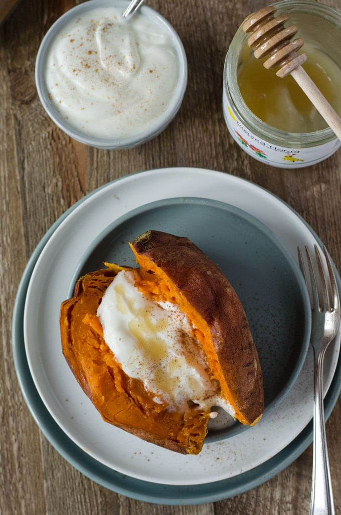 Süßkartoffel halbiert und offen auf einem grauen Teller von oben fotografiert