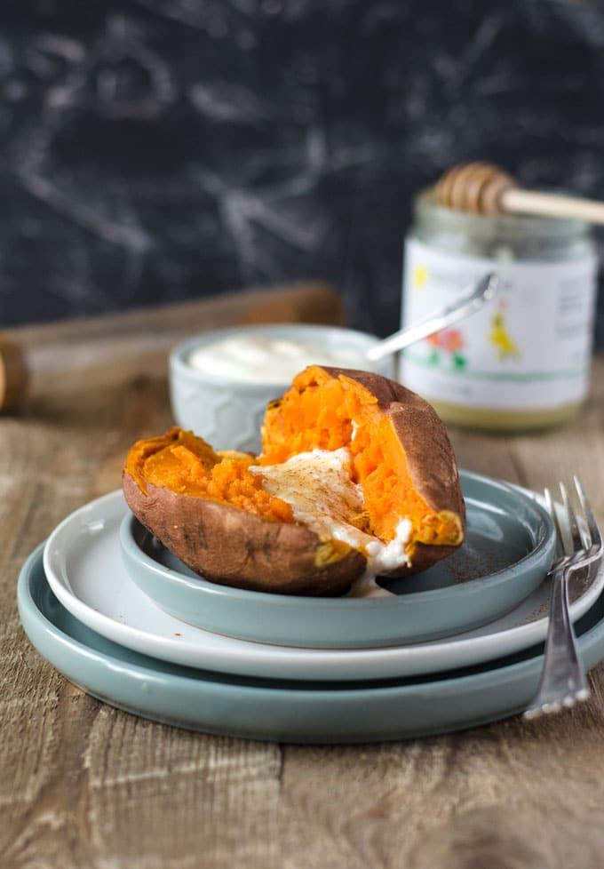 gegarte Süßkartoffel, halbiert auf drei Tellern mit Honig und Jogurt im Hintergrund