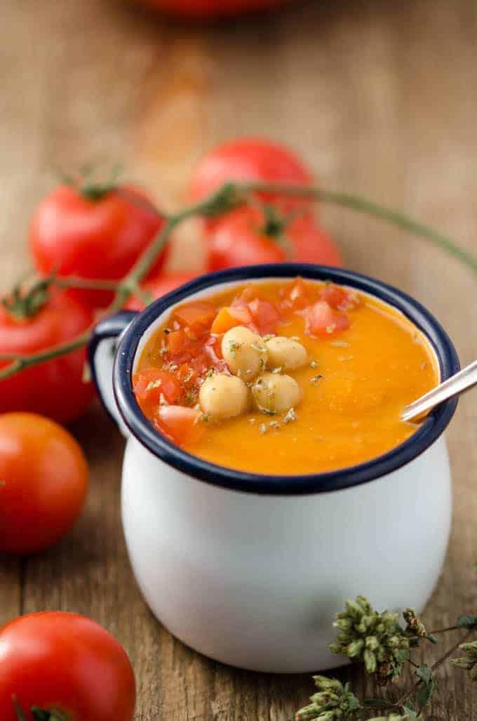 Kichererbsen-Tomatensuppe in weißer Emailtasse mit blauem Rand