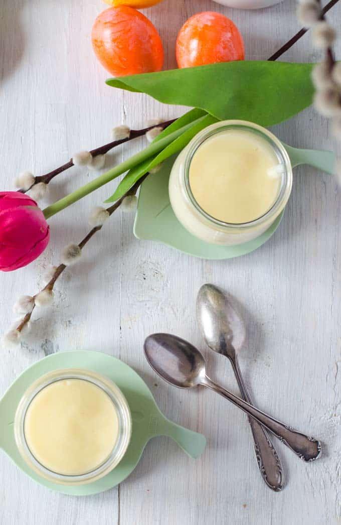 zwei Gläser mit hellem Pudding von oben fdotografiert, frühlingshaft dekoriert