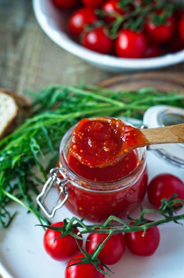 Tomaten-Chili-Konfitüre in einem Glas mit Deckel auf einem Löffel