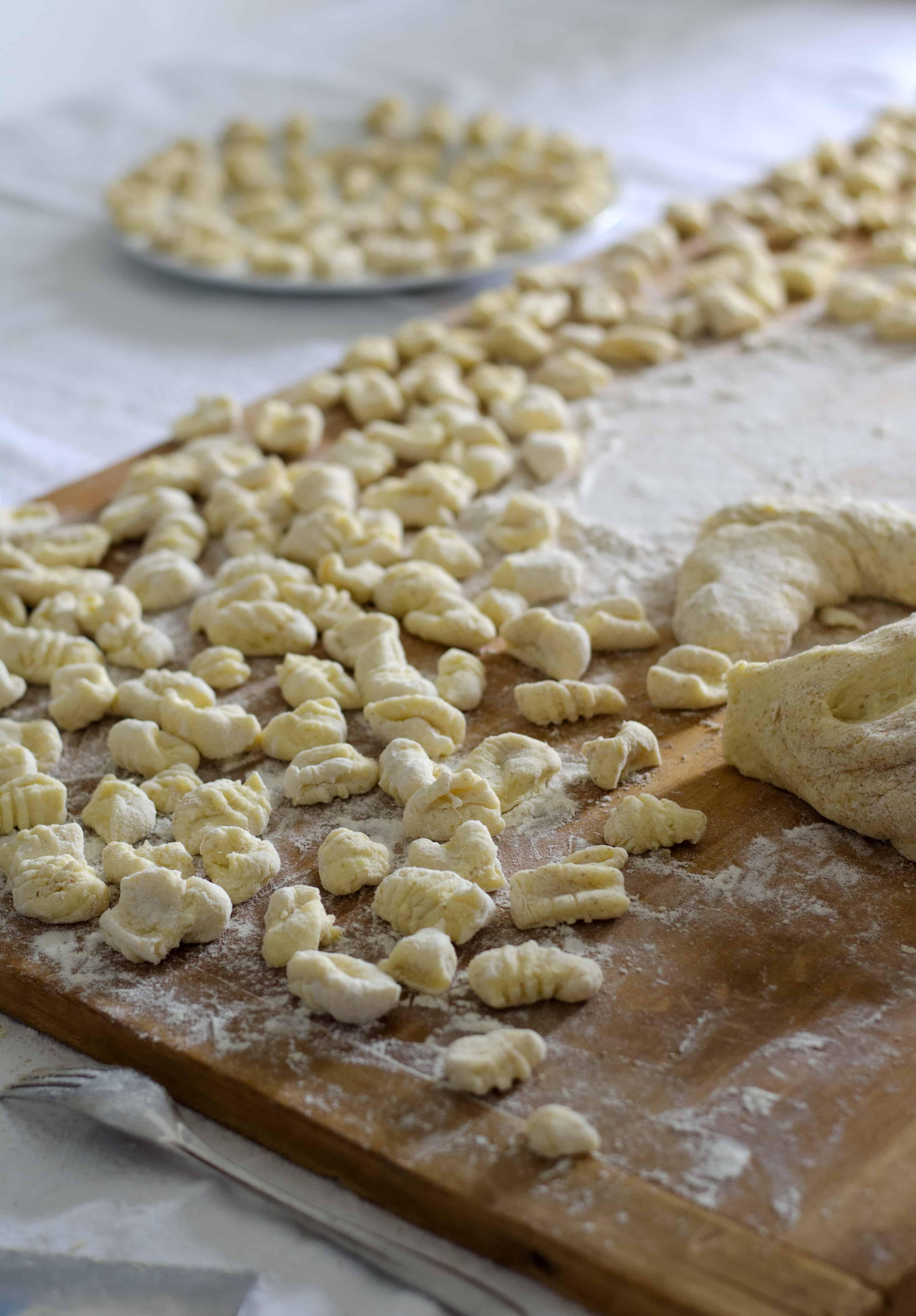 Gnocchi und Gnocchiteig und etwas Mehl auf einem Holfbrett