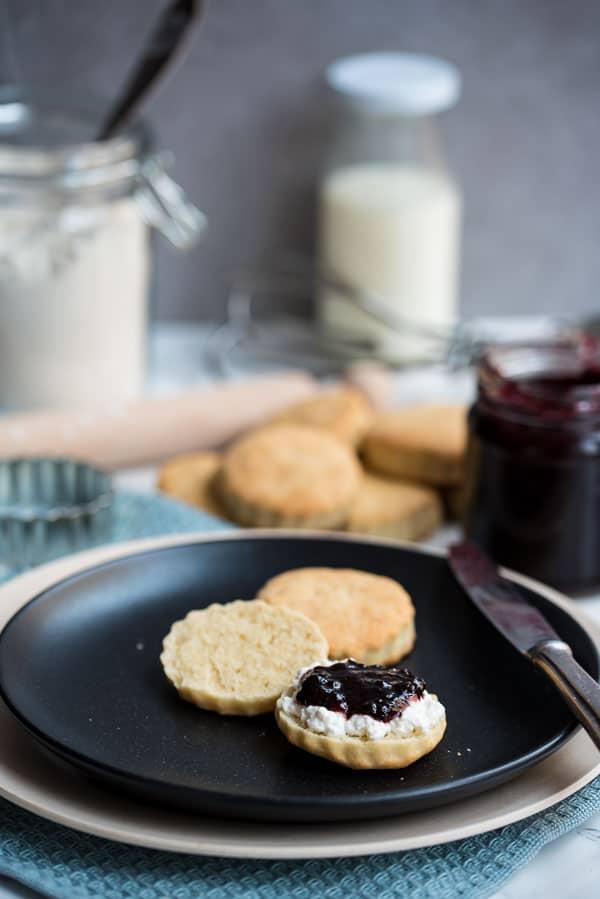 Cream Scones aufgeschnitten und mit Hüttenkäse und Beerenkonfitüre auf einem schwarzen Teller