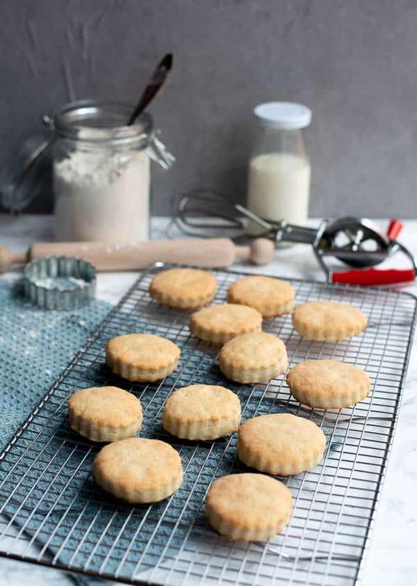 Cream Scones auf einem Kuchengitter mit Backutensilien im Hintergrund