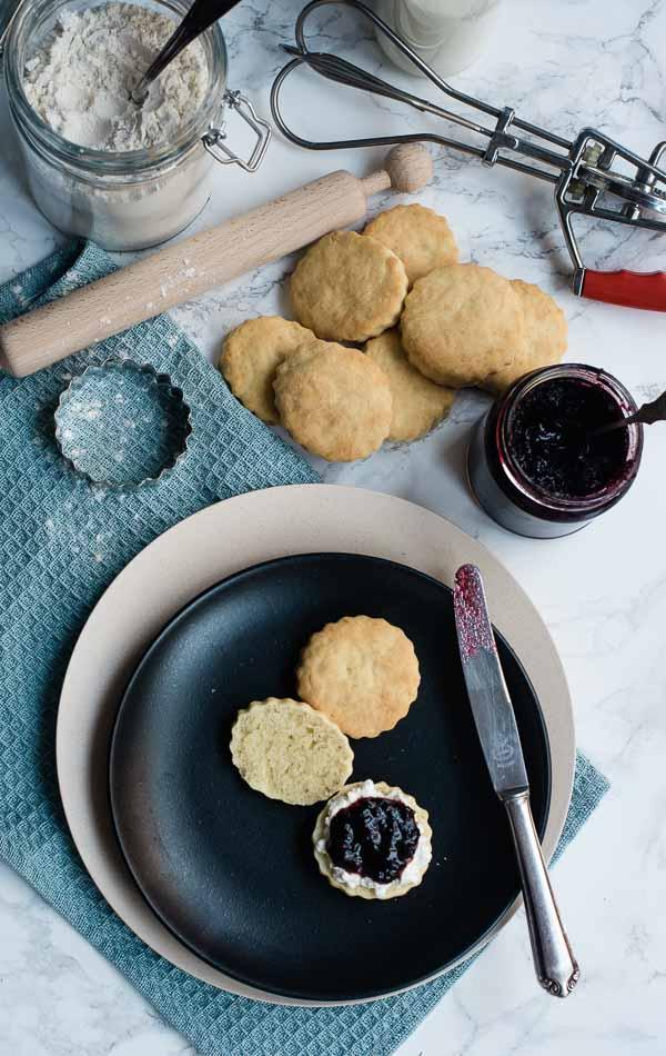 Cream Scones aufgeschnitten und mit Hüttenkäse und Beerenkonfitüre auf einem schwarzen Teller von oben fotofrafiert
