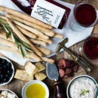 Eine Platte mit Fingerfood, Grissini, Dip, Oliven und Rose von oben fotografiert.