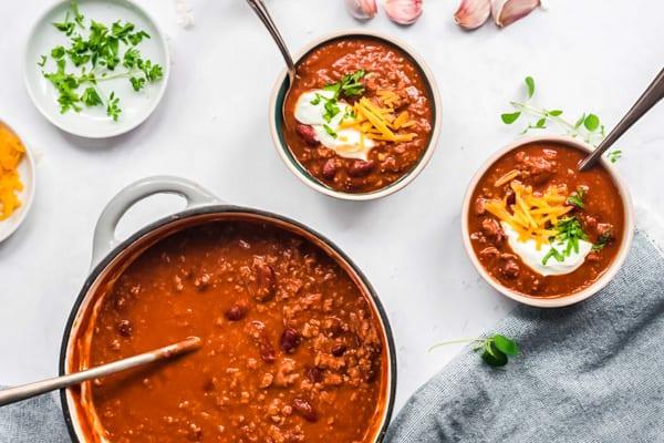 Ein Topf und zwei Schüsseln mit Chili con Carne von oben fotografiert