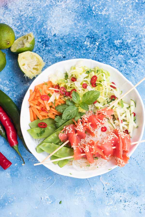 Glasnudelsalat mit Gemüse und Lachsspießen auf einem weißen Teller von oben fotografiert. Zu sehen ist außde Chilischoten und Limetten.