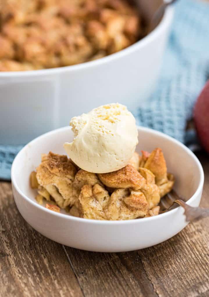 Nahaufname einer Portion Brotauflauf mit einer Kugel Vanilleeis in weißer Dessertschale
