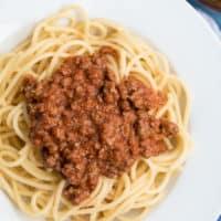 Spagetti Bolgnese auf einem weißen Teller auf einem blau-weiß gestreiften Tuch