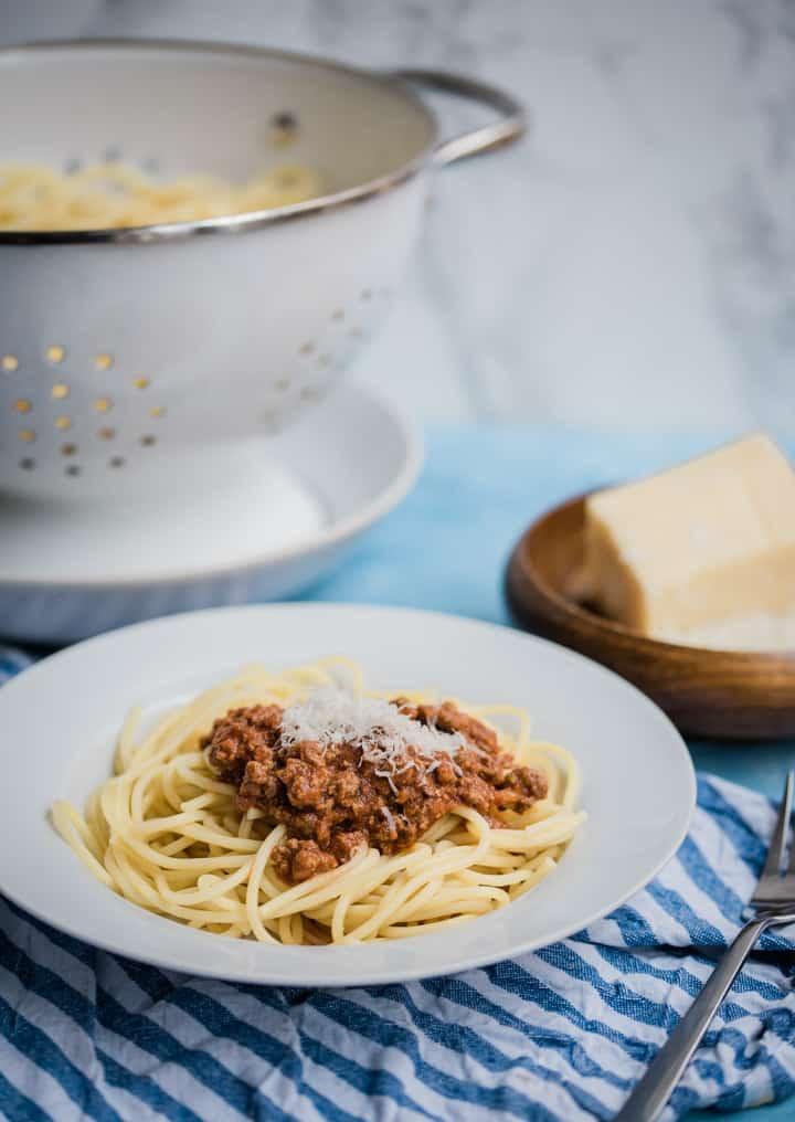 Bolognese mit Parmesan auf einem weißen Teller. Käse und Nudelsieb im Hintergrund.