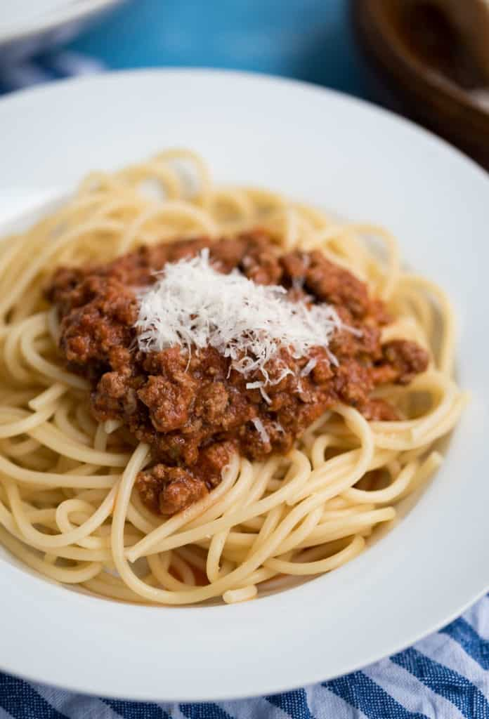 Spagetti Bolognese mit geriebenem Parmesan auf einem weißen Teller mit Rand, Nachaufnahme
