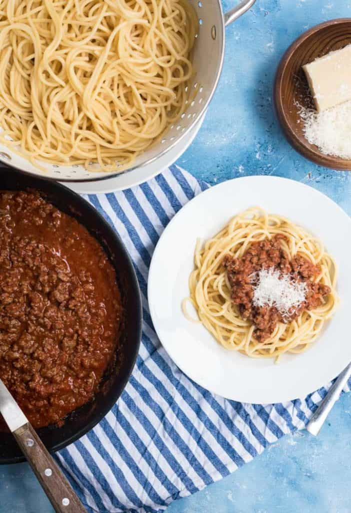 Spagetti Bolognese auf einem weißen Teller, Sauce in einer Pfanne und Nudeln in einem Sieb von oben